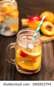 Mason jar glass of homemade peach iced water on a rustic wooden background