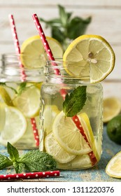 Mason jar glass of lemon lemonade with lemons and straw on table and wooden background. Cold summer beredge. Mojito drink. Lemon water
