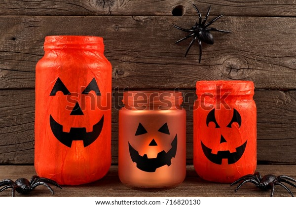 Mason jar Halloween Jack o Lanterns against an old wood background