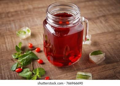 Mason jar with healthy goji juice on wooden table