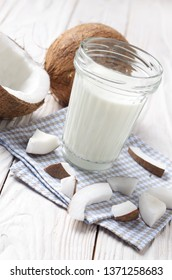 Mason jar of milk or yogurt on blue napkin on white wooden table with coconut aside