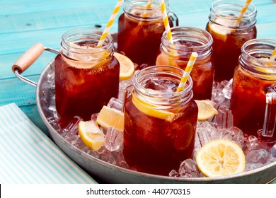Mason jar mugs filled with iced tea and fresh lemon with yellow swirled straw on ice in round steel tub sitting on bright blue wooden table with blue and white striped napkin