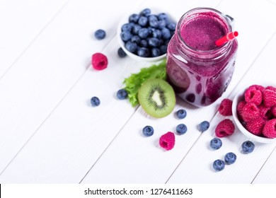 Mason jars with blueberry and raspberry fresh smoothie, top view on white wooden background, no people