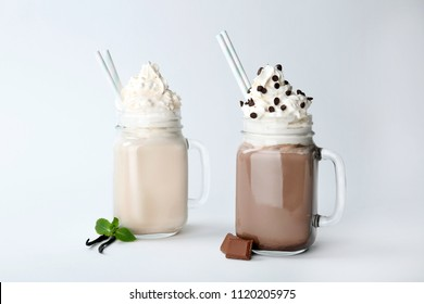 Mason jars with delicious milk shakes on white background