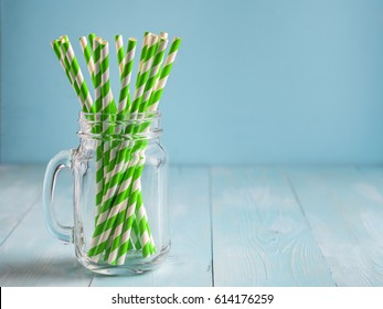 Mason jars with green paper straws on blue wooden background. Ideal for summer drinks and smoothies. Copy space