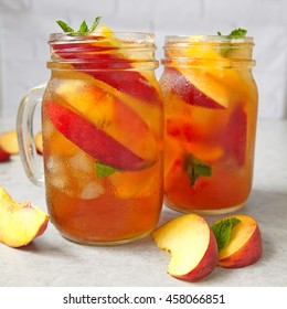 Mason jars of peach tea with ice