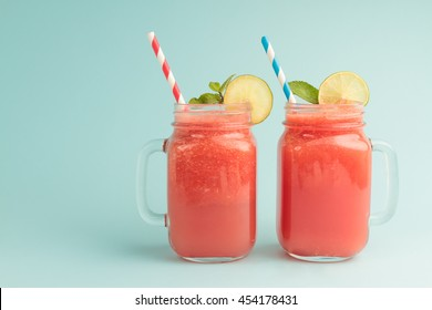 Mason jars of tasty watermelon drink on blue background with copyspace