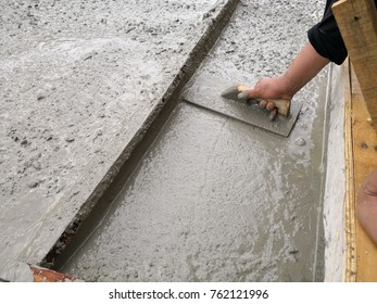 Mason leveling and screeding concrete floor base with square trowel.