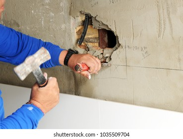 Mason making a hole in wall with hammer and chisel to place an electrical box for plugs during house reform