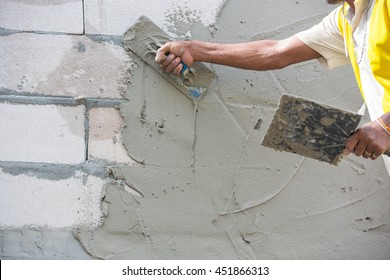 Mason plastering the concrete to build wall, Construction under  building with mason plastering concrete to brick wall