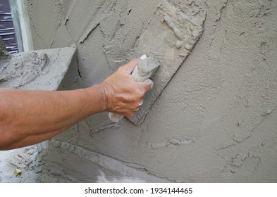 Mason plasters new cement with wooden trowel on the wall