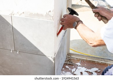the mason prepares the wall with a chisel before laying a ceramic tile