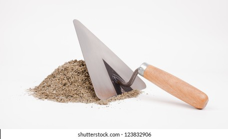 mason trowel and sand pile isolated on white