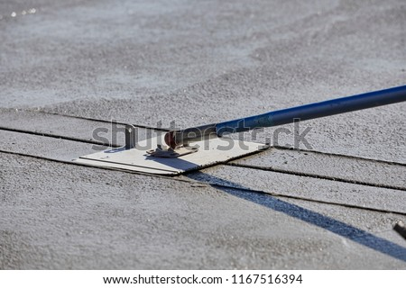 A mason using a concrete edger  to finish a newly poured concrete slab with shallow depth of field
