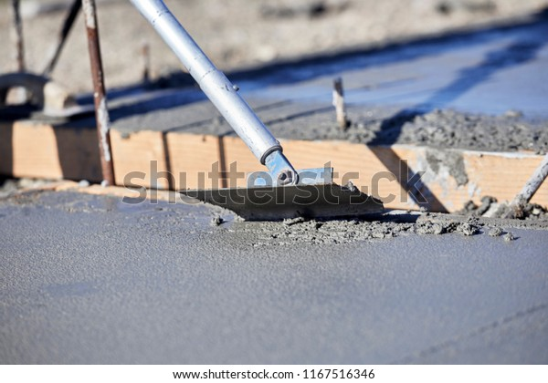 A mason using a concrete groover to finish a newly poured concrete slab