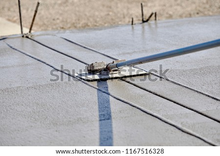 A mason using a concrete groover with a weight on it to finish a newly poured concrete slab with shallow depth of field