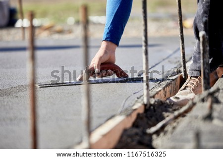 A mason using a concrete trowel to finish a newly poured concrete slab with shallow depth of field