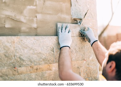 mason worker installing stone tiles on wall on construction site