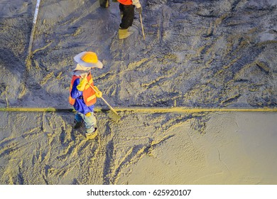 Mason worker leveling concrete with trowels, mason hands spreading poured concrete. Concreting workers are leveling poured liquid concrete on a steel reinforcement to form strong floor slab.