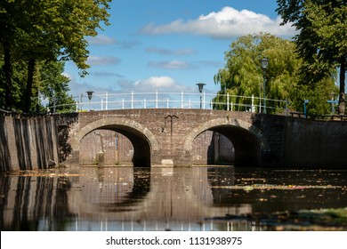 Masonry brick old bridge with a white wrought iron railing. Atmospheric photo of historical waterworks in the old hanseatic city of Kampen in Overijssel, the Netherlands.
