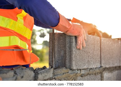 masonry construction worker in standard safety uniform install concrete block wall on new home construction site