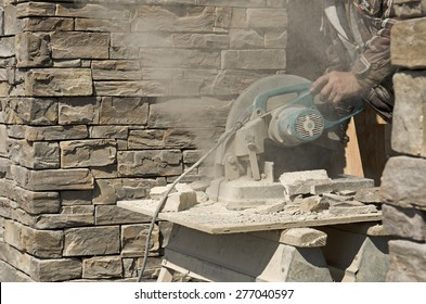 Masonry contractor using a dry circular tile or rock cutting saw to trim rock siding for a home installation