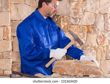 Masonry mason stonecutter man with hammer working on stone wall construction