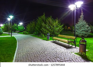 Masonry on the walkway in the green park in front of the Volga Embankment, a bench under the lamppost on a clean street with dustbins in the dark. Night Astrakhan City, Russia.
