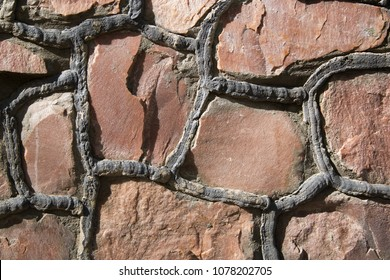 Masonry stone wall with irregular pattern, seamless texture or background