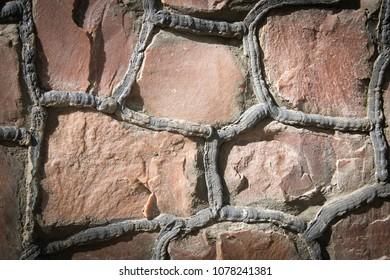 Masonry stone wall with irregular pattern, stonework texture or background. Closeup. Vignetted