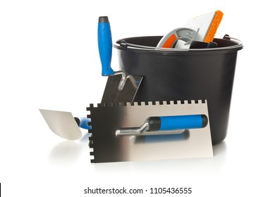 Masonry tools - trowels, notched trowel and mortar bucket - on white background
