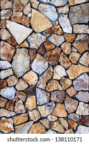 Masonry Wall of colors stones with irregular pattern, background