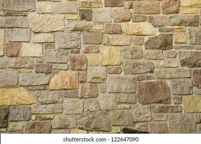 A masonry wall of multicolored stones or blocks
