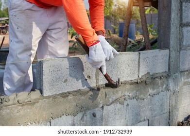masonry worker make concrete wall by cement block and plaster at construction site