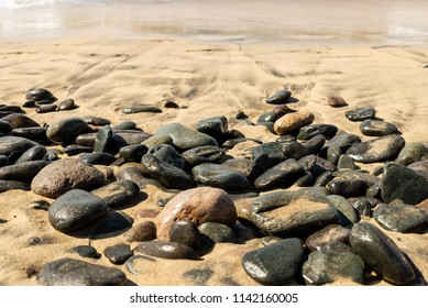 Maspalomas, Canarias islands/ Spain-July 22, 2018: Gray stones on sand from Sahara desert and distance view of blue Atlantic ocean and beach on Canarias island, Gran Canaria.