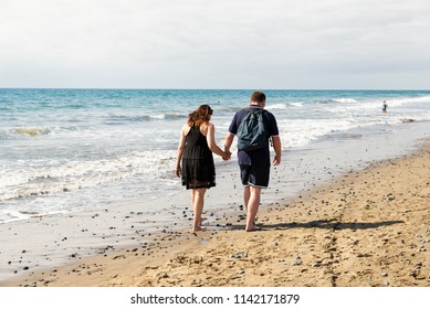 Maspalomas, Canarias islands/ Spain-July 22, 2018: Couple of man and woman walking on Canarias sand from Sahara desert, view of wet foot traces. Blue Atlantic ocean and beach on Gran Canaria.