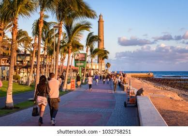 MASPALOMAS, GRAN CANARIA. JAN. 27, 2018. Tourist people stroll at sunset on promenade along palm trees and beach to lighthouse Faro de Maspalomas. Maspalomas, Gran Canaria.