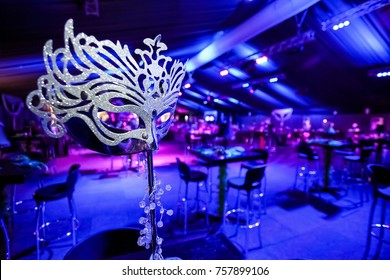 Masquerade Ball Mask next to a checkered dance floor with dancers in the background with blue and purple lighting