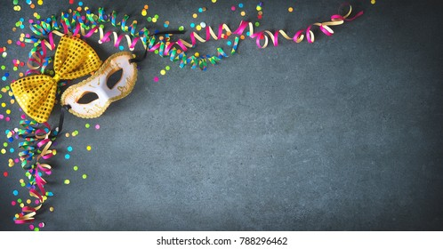 Masquerade decorations with streamers and confetti on dark background with copy space