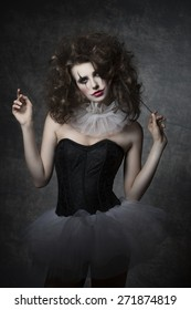 masquerade woman with vintage dancer dress, sad clown make-up and uncombed hair. Romantic fashion portrait