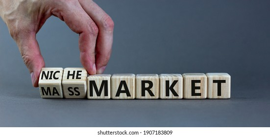 Mass or niche market symbol. Businessman flips wooden cubes and changes words 'mass market' to 'niche market'. Beautiful grey background, copy space. Business and mass or niche market concept.