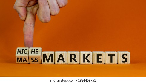 Mass or niche markets symbol. Businessman turns wooden cubes and changed words 'mass markets' to 'niche markets'. Beautiful orange background, copy space. Business and mass or niche markets concept.