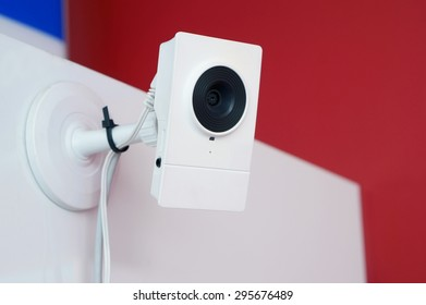 The mass production white camera of video  supervision is fixed on a wall of office. Art soft selective focus