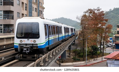 Mass Rapid Transit (MRT) train on the rail track with modern building in the city, transportation in Taipei, Taiwan