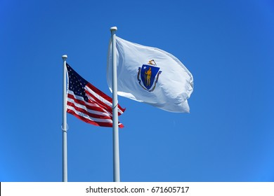 Massachusetts flag and USA national flag waving on the pole in the wind
