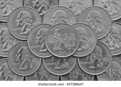 Massachusetts State and coins of USA. Pile of the US quarter coins with George Washington and on the top a quarter of Massachusetts State.