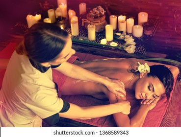 Massage and aromatherapy of woman getting rid of cramps in spa candle salon with healer.