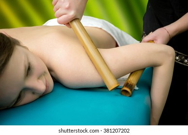Massage with bamboo sticks for a young girl at the massage parlor