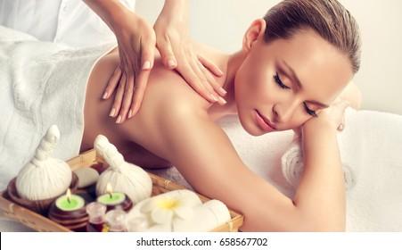 Massage and body  care. Spa body massage treatment. Woman having massage in the spa salon . Massage woman hands