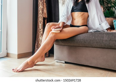 Massage with a dry brush. A girl in a white shirt massages her legs sitting on a cofa. Anti-cellulite, peeling, cosmetic procedures. Home skincare concept.